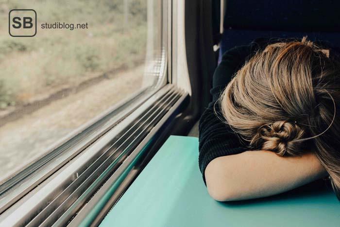 Junge Frau hat den Kopf erschöpf auf dem Ellbogen abgelegt auf einem Tisch im Zug am Fenster - Burnout.