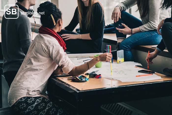 Studierende sitzen gemeinsam um einen Tisch und diskutieren die vor ihnen liegenden Unterlagen - Kommilitone.