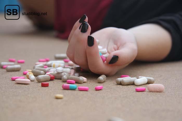 Frauenhand mit schwarz lackierten Fingernägeln liegt mit Handrücken auf dem Boden, rund herum und in der halb geöffneten Hand liegen verschiedenste Tabletten - Nebenwirkungen.