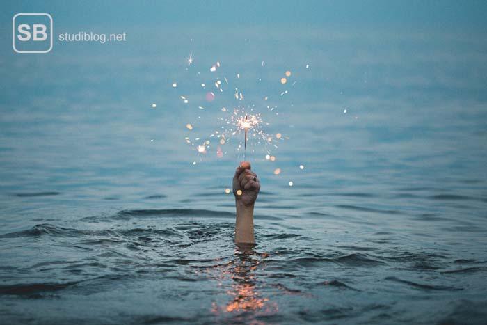Eine Hand streckt sich aus dem Meer mit einem Sternwerfer in der Hand - medizinische Psychologie im Studium.