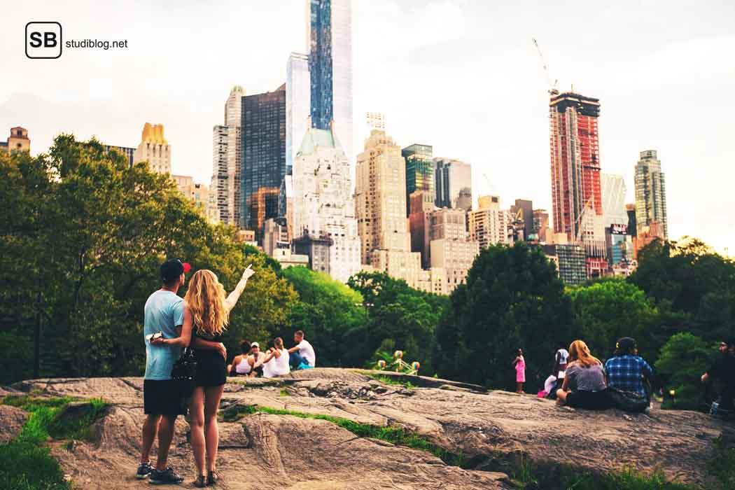 Pärchen mit Blick auf die Skyline einer Großstadt - Blick hinter die Fassade von Airbnb