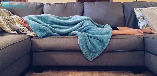 Richtig Pause machen: Mann liegt auf der Couch und zieht sich die Decke über den Kopf
