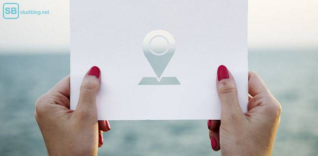 Student's travel guide: A woman is holding a piece of paper with a destination marker cut out of it