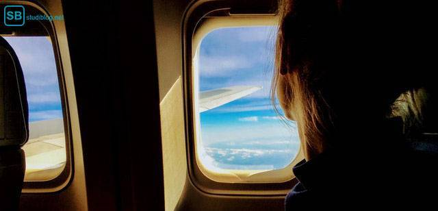 Student's travel guide: A girl is looking out of an airplane window