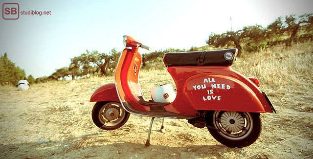 Student's travel guide: A red scooter is standing at a beach. It has 'All you need is love' written on it.