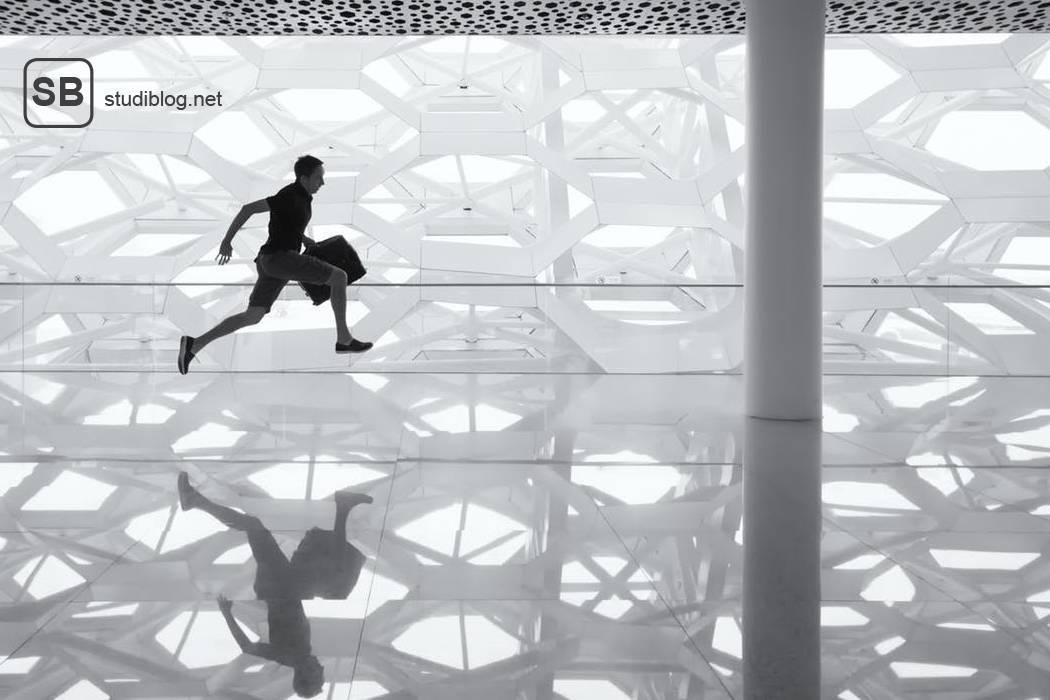 Bewerber auf dem Weg zu seiner möglichen Festanstellung bewegt sich springend über eine Fläche aus Sicherheitsglas, in der Hand hat er eine Aktentasche