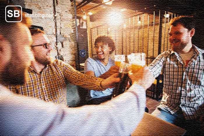 Freitagabend Freundesrunde in einer Kneipe mit Bier in der Hand