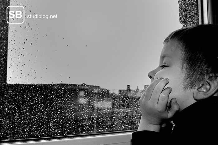 Ein Kind, das aus dem Fenster starrt - Sinnbild für sich langweilen