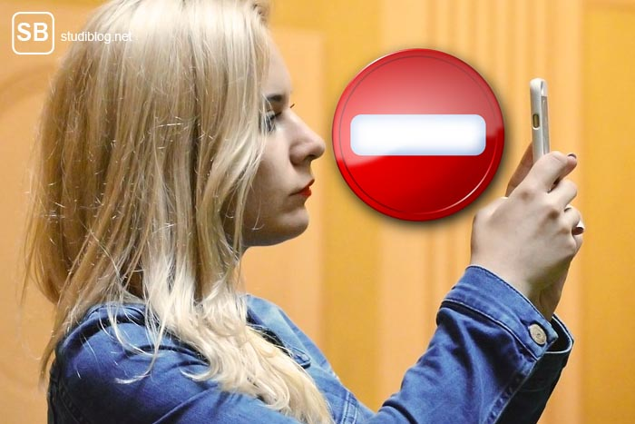 Oberflächlich - Studentin macht ein Selfie, zwischen ihrem Gesicht und dem Handy befindet sich ein Stop-Zeichen