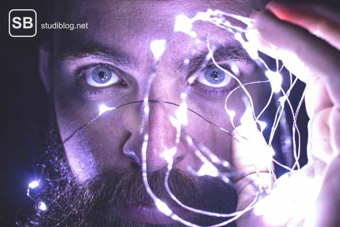 Mann mit Bart und Leuchtdraht vor dem Gesicht zum Thema Gehirndoping um jeden Preis?