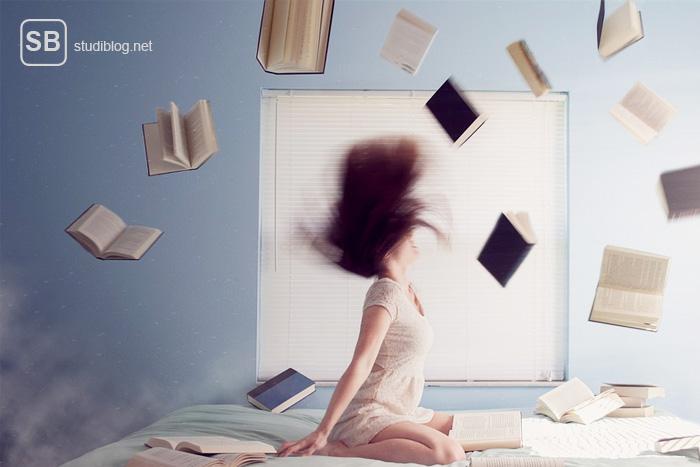 Lerntypen - Studentin auf dem Bett mit fliegenden Büchern