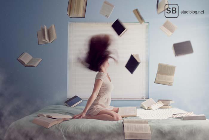 Studentin auf dem Bett mit fliegenden Büchern um sich herum