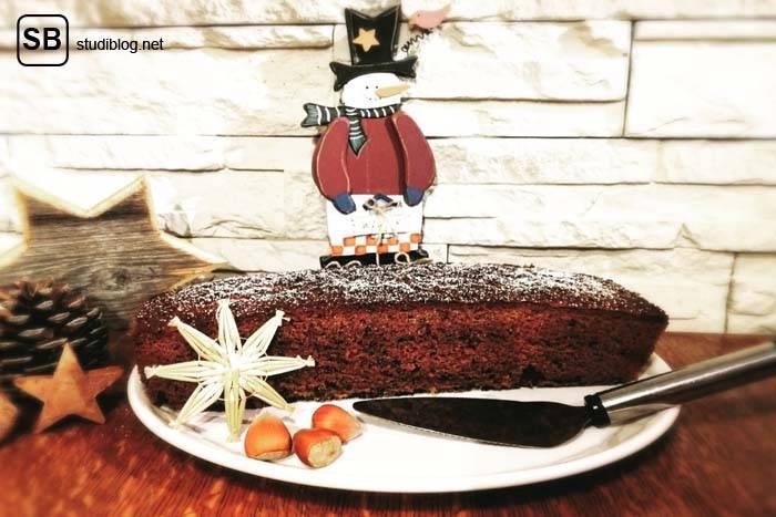 Saftiger Rotweinkuchen mit Puderzucker bestreut auf einem weißen Teller - Rezept zum Nachbacken.