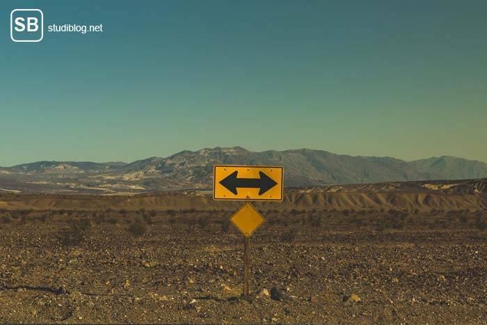 Gelbes Schild in unbewohnten Gebiet auf dem zwei Pfeile in entgegengesetzte Richtungen zeigen - Studium: Realität vs. was Andere denken.