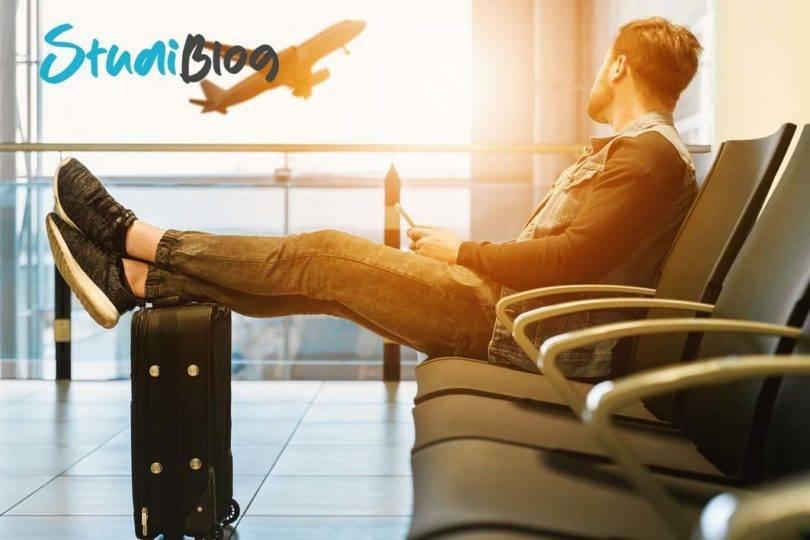 Heimweh und Fernweh: Ein Backpacker sitzt in freudiger Erwartung in einer Flughalle und wartet auf sein Boarding.