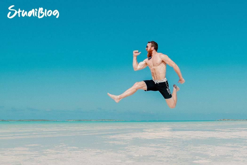allein reisen - student springt am sandstrand im hintergrund das türkise meer