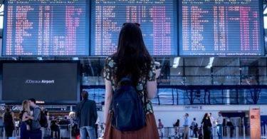 allein reisen studentin steht vor infotafel am flughafen